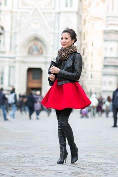 This combo of a black leather moto jacket and a red fit and flare dress is a safe bet for an effortlessly cool look. Go for a pair of black leather thigh high boots to va-va-voom your outfit.  Shop this look for $97:  http://lookastic.com/women/looks/scarf-biker-jacket-clutch-skater-dress-tights-over-the-knee-boots/7895  — Brown Leopard Scarf  — Black Leather Biker Jacket  — Black Leather Clutch  — Red Skater Dress  — Black Wool Tights  — Black Leather Over The Knee Boots