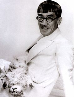 """'The artist known as Foujita moved from Tokyo to Paris 100 years ago...the artist had been known to sport """"a band around his forehead, a cape hanging from his shoulder, a necklace of large stones, a woman's bag, and sandals,"""" further noting that """"This attire had not kept women from throwing themselves at him.""""'  Via Strange Flowers."""