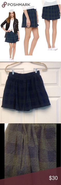 Holly Go Lightly Plaid Skirt A flirty Free People skirt cut from tactile bouclé knit and subtly patterned in muted plaid. Undone pleats add movement to the full silhouette, and a smocked elastic back panel relaxes the wide waistband. Welt hip pockets. Lined. Fabric: bouclé knit. Shell: 60% cotton/40% polyester. Lining: 100% rayon. Free People Skirts Mini