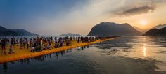 The People Walking On The Water - For sixteen days – June 18 through July 3, 2016 – Italy's Lake Iseo is being reimagined. 100,000 square meters of shimmering yellow fabric, carried by a modular floating dock system of 220,000 high-density polyethylene cubes, undulate with the movement of the waves as The Floating Piers rise just above the surface of the water.  Visitors can experience this work of art, created by famous artist Christo, by walking on it from Sulzano to Monte Isola and to…