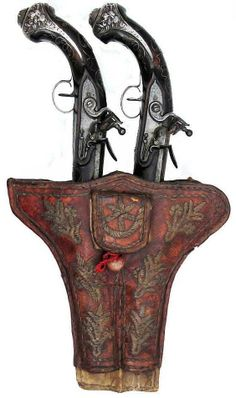 Ottoman flintlock kubur (holster pistols), 18th c, hardwood stocks inlaid with wire in rococo designs, the hallmarked silver furniture cast and chased with stands of arms, crescent and turban. Engraved motif locks, stepped and swamped barrels chiseled and inlaid with crescents in gold and silver. In their red leather double holster, embroidered in characteristic Ottoman motifs with silvered thread. Overall length 31.8 cm.
