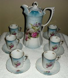 Lovely Snow Mums Roses Floral RS Prussia Chocolate Pot Set. This set features the chocolate pot with lid, six cups and sixsaucers. All pieces are decorated with Snow Mums and Roses which is a common floral pattern used by R.S. Prussia pieces.