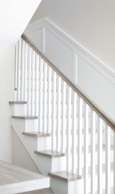 The staircase features a clean, neutral look thanks to the square white spindles and white oak handrail and flooring. Patterson Custom Homes. Brandon Architects, Inc. Oak Handrail, Stair Spindles, Staircase Railings, Staircase Design, Bannister, Staircases, Oak Banister, Staircase Ideas, Hallway Ideas