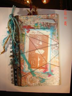 This journal was made by covering a basic wire bound notebook and embellishing with string, beads, fiber...The inside has a pocket to hold book mark.
