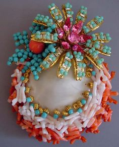 VRBA brooch, real sea shell (Lazarus Jewel Box that has been polished down to the mother-of-pearl) with artificial graduated hue stick coral, aqua glass beads and pink and yellow rhinestones set in gold tone flower brooch  http://www.morninggloryantiques.com