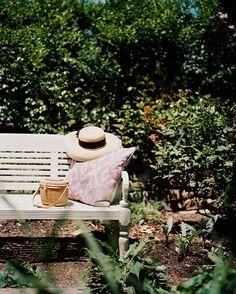 Garden - An outdoor bench, an ikat pillow, and a sun hat make for a quiet spot to read in Dominique Browning's Rhode Island garden.