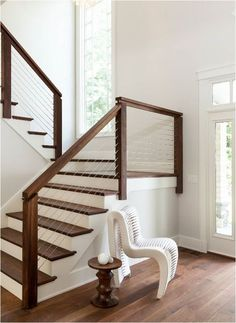 dark wood and cable railing with white steps look chic and modern