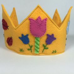 This felt birthday crown is sure to make your little one stand out with style! All shapes/flowers/embellishments are made by hand by me, making each crown one-of-a-kind! If you would like other colors or themes, just message me and I will be glad to make it to your liking!    Crown will be finished with stitched edging all the way around, fitted with an elastic band around the back so it stays put on your childs head