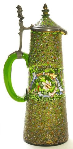 A Moser tankard pitcher, cylindrical in green decorated with band of polychrome scrolling framed with overall gold scrolling of blue, red and white flowers, glass lid with like desogn, metal flip handle with beer drinking gnome. Czechoslovakia, circa 1893-2007