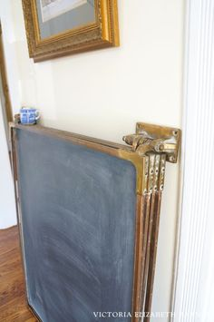 We are DIY-ing a falling-down Victorian house, one room at a time… and the BEST part is the decorating! This antique, brass hinged chalkboard is one of my favorite salvaged finds!!