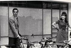 Alain Delon and Leslie Caron park their bikes.