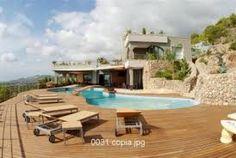 Superbe villa avec belle piscine avec cascade naturelle, entourée d'une terrasse en bois et magnifique jardin avec plantes indigènes, palmiers et pelouse