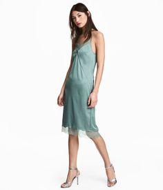 Støvet grøn. Knælang kjole i satin med blondedetaljer. Kjolen har smalle, justerbare skulderstropper foroven. Er dybt skåret i ryggen og har slids bagpå.