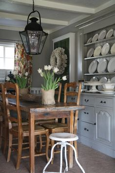 Beautiful dining room with lantern hung over table CABINET HANDLES AND CABINET DESIGN AND PENDENT LIGHT