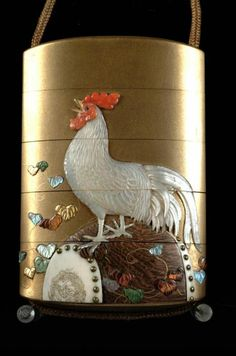 This four box inro depicts a cockerel upon a barrel, the reverse depicts a hen and three chicks. The interior is red-brown speckled gold.