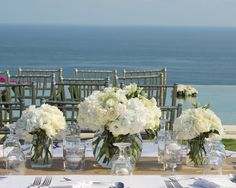 Cluster table centerpiece of white lisianthus, white hydrangeas, ivory roses, white spray roses, tuberoses blooms