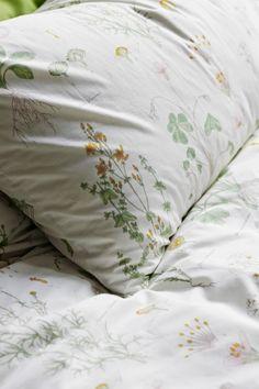 VIGDIS Kissenbezug in Grün und Bettdeckenbezug mit einem botanischen Muster.