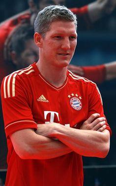 Bastian Schweinsteiger poses in the new FC Bayern Muenchen home jersey-Bundesliga