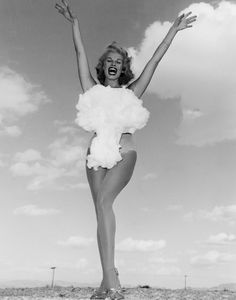 "Copa Room showgirl Lee A. Merlin poses in a cotton mushroom cloud swimsuit as she is crowned Miss Atomic Bomb in this 1957 photograph. Above-ground nuclear testing was a major public attraction during the late 1950s and began to infiltrate every aspect of society, from household goods to football teams naming themselves the ""Atoms."" Inspired by the cultural phenomena, Las Vegas decided to combine two of its major attractions, nuclear bombs and showgirls, into a beauty contest."