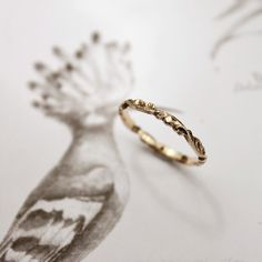 2mm width, 9ct gold floral carved ring.All our engraving is done entirely by hand, using methods unchanged in hundreds of years.This pattern has been achieved using tiny sharp chisels, by our very experienced engraver here in London.Each one is engraved and carved separately, giving each ring it's own unique hand finish. hallmarked inside the ring to show the metals purity.All of our wedding rings are made to size, and this ring will be made and dispatched within...