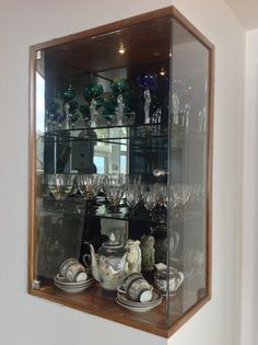 Glass cabinet with smokey mirror back - same wood finish as cabinetry. New home to respective grandparents' Norwegian glassware and tea set