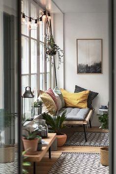 Banquette de jardin dans le salon, tapis ethnique et plantes d'intérieur
