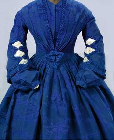 Royal blue damask dress, late 1850s-early 1860s. In one piece, the bodice points and has pleated detail to sloping shoulders. The bell sleeves have net insets and separate matching undersleeves and white gloves worked in blue-purple.