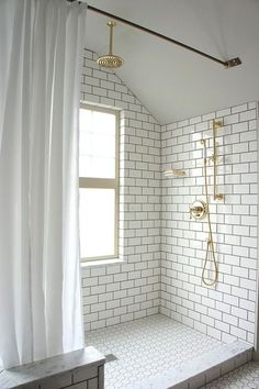 Walk-in shower with dark grouted subway tile, brass fixtures, and curtain instead of glass doors.
