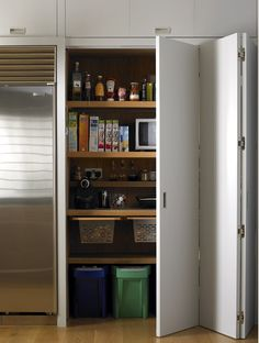 Bi-fold doors reveal a pantry and larder storage cupboard, with space for dry foods, recycling bins and appliances. Kitchen Designed by Giles Slater for Figura