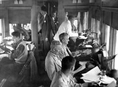 A view of the Press Car on President Truman's train showing reporters working at typewriters. The reporters were traveling with Harry S. Truman during while he was campaigning for the 1948 election.