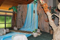 Rainforest / Jungle theme VBS - waterfall made from a wooden frame, with crumpled brown craft paper stapled over it. Water made from blue plastic table cover roll.this looks doable and affordable Safari Crafts, Jungle Crafts, Vbs Crafts, Church Crafts, Jungle Decorations, Rainforest Theme, Vbs Themes, Island Theme, Bible School Crafts