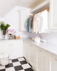 White laundry room with black and white tile design and built in hanging rack | Pink Peonies