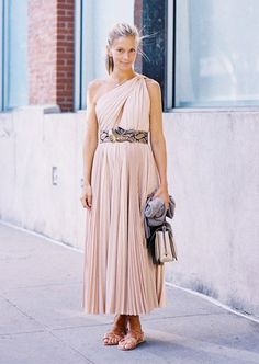 A pink one-shoulder dress is worn with a snakeskin belt, lace-up sandals and a top handle bag