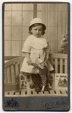 Wonderful antique cabinet card photo of little girl with clown doll.