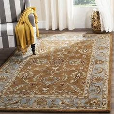 Showcasing a Persian-inspired motif in brown and blue, this hand-tufted wool rug lends classic appeal to your living room or master suite.