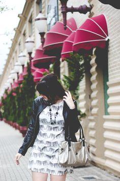 Look neutro com vestido com estampa de elefantes, jaqueta de couro, sapatilha e bolsa prateada