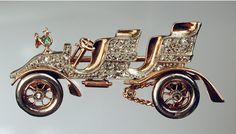 Motorcar, Car brooch, with old cut silver set platinum body, diamond platinum hubs, platinum tyres, gold and emerald lamp, and exquisite gold details, English, circa 1902.