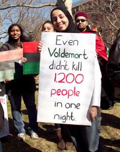 """""""Over in the states, there were quite a few protests in support of those fighting their government's oppression and while most of the signs showing solidarity were fairly straight-laced, this young woman stood out from the crowd with her geeky poster pointing out that even Voldemort never killed as many people as Gaddafi had executed during one night of the rebellion. Image by Collin David Anderson."""""""