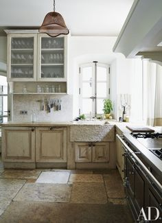 The kitchen features reclaimed stone pavers from Burgundy and a 17th-century Provençal sink.
