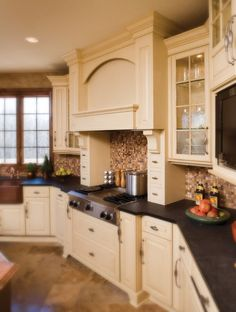 White cabinets, dark counter tops, copper sink, tile floor