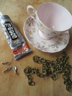 Birdfeeder: a cup and saucer, three large jewelry bails, about 42 inches of sturdy chain, and some E6000 glue.
