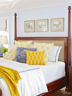 Barely-there gray walls add the perfect amount of dimension to this bedroom. White bedding is a slight contrast to the walls and provides a perfect backdrop to yellow and navy patterned pillows. The dark wood bed stands out against the rest of the room and is the main focal point of the bedroom.