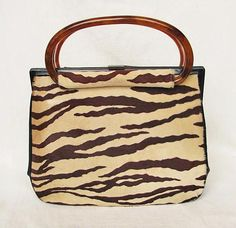 Very nice vintage 1950s KORET oversized handbag made of tiger stripe-patterned fur calf skin w/black calfskin leather sides and bottom.  Tubular tortoiseshell lucite double handle.  Leather-covered hinged frame w/gold metal top clasp.  Black genuine patent leather lining.  One side has a zippered pocket.  The other side has 2 open pockets, one holding a mirror in a gold faille pouch.  All of the pockets are lined w/gold faille.  The interior is divided by a black and gold faille-lined inner…