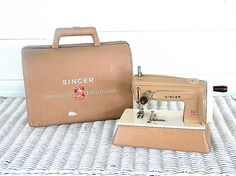 "Singer Sewhandy Model with Case - Toy Sewing Machine. This is a fully functioning toy Singer sewing machine made in Great Britain (and signed as such) in the 1960's. It is not electric but rather a wind up, you row the knob on the side to make the needle stitch. The case is the same exact tan color as the machine and is also signed ""SINGER, SEWING MACHINE"" with the ""S"" emblem."