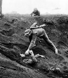 March 16, 1945: A U.S. Marine approaches a Japanese soldier on Iwo Jima, Japan during World War II. The Japanese soldier was buried for 1 1/2 days in this shell hole playing dead and ready with a live grenade inches away from his hand. The Marines feared he might be further booby trapped underneath his body after knocking the grenade to the bottom of the shell hole. Promising no resistance, the prisoner is given a cigarette he asked for and was dragged free from the hole.