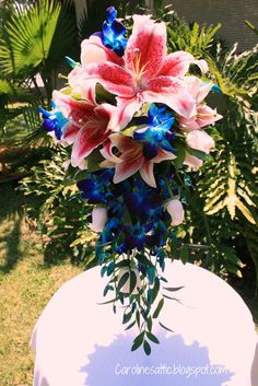 Tropical cascade bridal bouquet with stargazers and orchids
