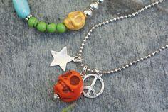Gekleurd howliet in vrolijke heldere kleuren gecombineerd met symbolen vormen samen een trendy en draagbaar sieraad
