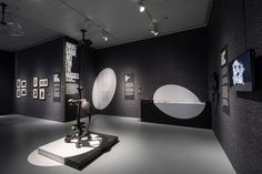 """Graphic """"spotlights""""—white circles painted on the walls and floor—are used to highlight works in the exhibition and create an atmosphere that suggests a television studio."""
