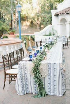 At this wedding, the bride and groom's chairs differed from the rest of the seats at the head table. The area was decorated with a fun tablecloth, a macramé runner, and a garland. onelove photography www.onelove-photo.com