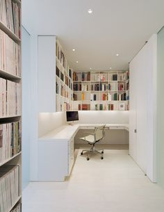 This home office with plenty of storage is in a white themed apartment in…